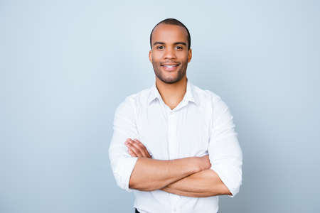 Photo pour Successful smiling young handsome mulatto american guy lawyer in formal outfit on pure background with crossed hands. So rich and confident, attractive and smart - image libre de droit