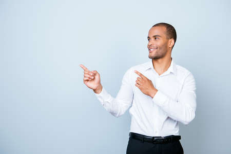 Foto de Young cheerful successful african entrepreneur on the pure light blue background is smiling, wearing formal wear and is pointing on a copyspace with his fingers - Imagen libre de derechos