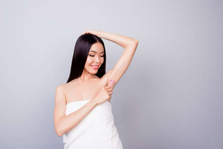 Photo pour So smooth and pure. Young cute asian lady with pink shaver is cutting her armpit hair, smiling, standing in the towel, on pure background - image libre de droit
