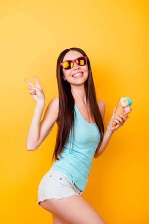Foto de Funky young asian lady is posing for vacation photo shot, wearing tourist`s outfit, glasses, holds ice cream, has a tempting sexy pose - Imagen libre de derechos