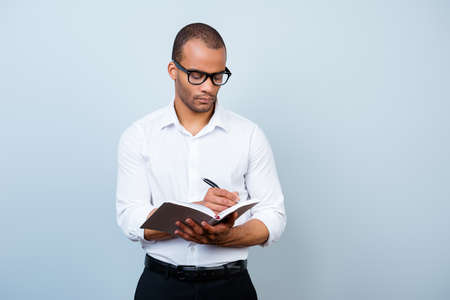 Photo for Education, work and success concept. Nerdy academic african professor is thoughtful, in glasses, holding a notebook and writes information - Royalty Free Image