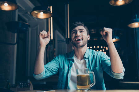 Photo pour Goal! Cheerful young man is happy because of the goal of his favourite team. He is watching game at the fancy cafe with a glass of beer. - image libre de droit