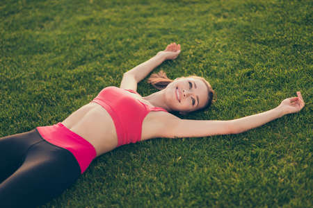 Photo pour Champion. Well done! Exhausted cheerful sportive woman is relaxing after a fitness workout, lying on the green grass in a spring park outdoors - image libre de droit