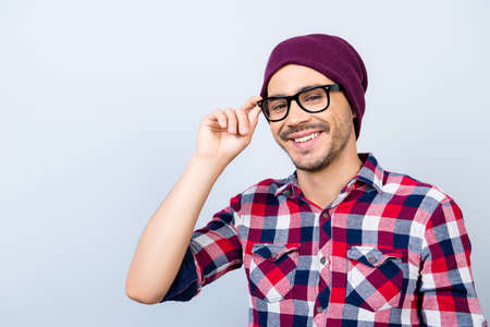Photo for Dreamy student hipster in a casual checkered shirt, black glasses, hat, smiling and looking at the camera, standing on  alight background - Royalty Free Image