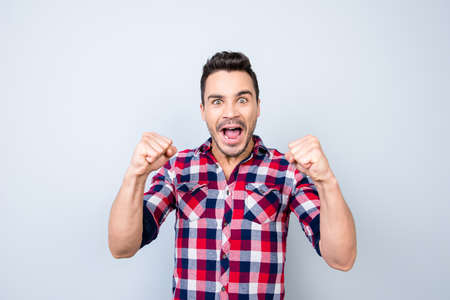 Photo for Young hipster is watching the sports game and is gesturing victory of his favourite team, in checkered shirt, on pure background - Royalty Free Image
