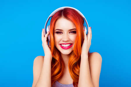 Photo for pretty girl is listening to music in big white earphones. Her smile is beaming, she is happy - Royalty Free Image