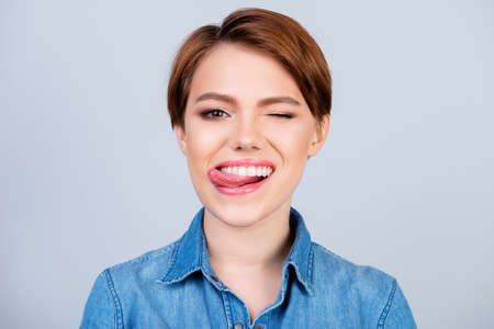 Foto de Close up portrait of happy pretty young girl with short hair and jeans shirt licking lips and giving a wink - Imagen libre de derechos