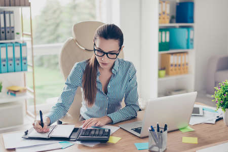 Photo pour Portrait of serious young businesswoman accountant in formal wear and with pony tale, sitting at her work place and doing notes - image libre de droit