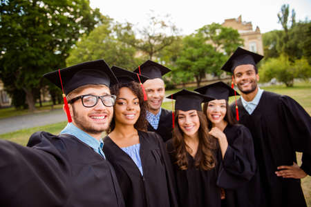 Photo pour Six international students are posing for selfie shot, that nerdy guy is taking, outside school building. Gathered, cheerful, smart and successful youth in mortar boards, gowns - image libre de droit