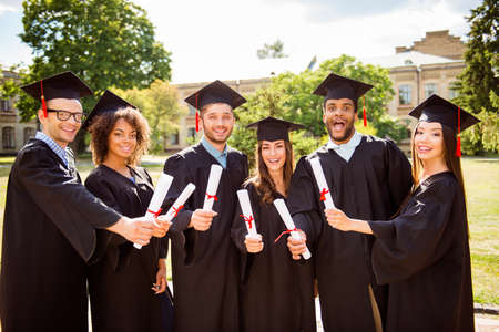 Photo for Six amazed successful attractive young graduates in black robes and hats finished their education, are smiling and bonding with diplomas in hands, behind is the collage building, nice sunny day - Royalty Free Image
