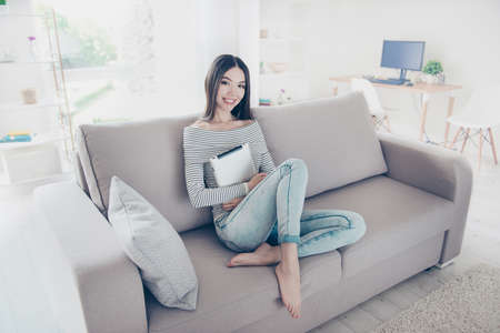 Photo for Young charming asian girl  is holding her tablet, sitting on beige couch indoors at home, wearing stripped clothes, jeans, barefoot, relaxing and enjoying - Royalty Free Image