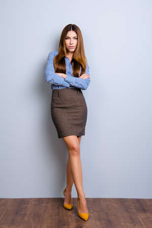 Photo for Full size photo of elegant business lady lawyer standing in flirty pose with crossed hands and legs. She looks so sexy and tempting - Royalty Free Image
