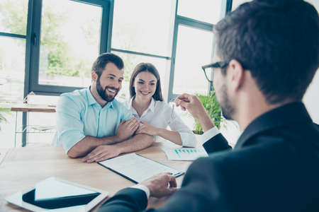 Photo pour Happy young couple is embracing, getting a key from their future apartment from a broker, and signing contract, all are dressed in formal outfits, nice light office design - image libre de droit