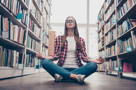 Photo pour Chilling, wellbeing, vitality, peace, wisdom, education, campus lifestyle. Low angle shot of young calm nerdy girl, practicing yoga in the lotus position on floor in archive room of library - image libre de droit