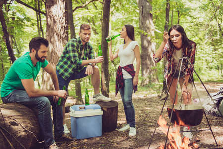 Photo for Chilling near the fire in a camp in sunny forest. Brunette girl is checking the meal in cattle, friends are having beer - Royalty Free Image