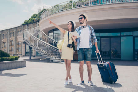 Photo pour Check this out! Happy married couple are on honey moon, in caps, eyewear and with camera, valises, outdoors, walking on nice spring day - image libre de droit