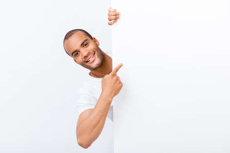 Photo for Happy amazed young mulatto guy is popping out from white blank banner, pointing at it with finger, wearing white t shirt, on white background - Royalty Free Image
