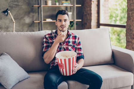 Foto de Portrait of impressed brunet attractive hipster with bristle in shirt eating pop corn while watching scary movie alone, shocked grimace, crazy emotions, wide open eyes, even stopped eating pop corn - Imagen libre de derechos