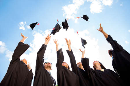 Foto de Low angle shot of cheerful group of six young multi ethnic graduates in black gowns, throwing up their hats in the air and celebrating, laughing, enjoying - Imagen libre de derechos