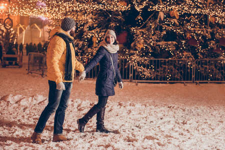 Photo for oung couple in love is walking in a park of attractions outdoors at the eve, enjoying, holding hands, dressed warm, looking at each other, huge christmas tree behind - Royalty Free Image