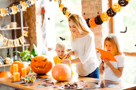Foto de Halloween mood. Blonde family of mother and two siblings are preparing for party, cutting decorations, making jackolantern, desktop with candles, candies, fall leaves, little black bats on windows - Imagen libre de derechos