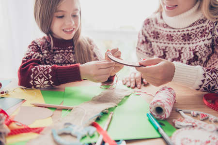 Foto de Happiness, upbringing, childhood, friendship, leisure, traditions x mas noel concept. Close up cropped of lovely blonde with her mommy doing handcraft activity, enjoying, desktop is full of materials - Imagen libre de derechos