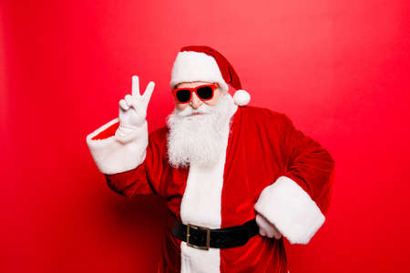 Foto de Cool funny playful naughty tourist santa grandfather showing peace signs, fooling around, in trendy specs, so confident. - Imagen libre de derechos