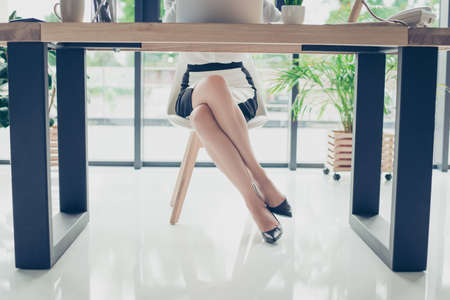 Foto de Close up cropped photo of attractive legs of the elegant stunning business lady in dark high hills shoes, skirt, she is sitting in the moden office, trendy chair and desk, shuining white floor - Imagen libre de derechos