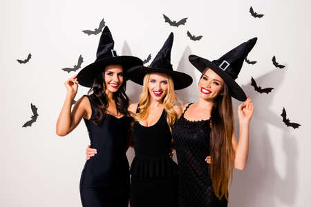 Photo for Group of three cute embracing seductive worlocks in carnival dresses, so slim and playful, with red lips, beaming smiles, in dark headwear, white wall background, scary small creatures vampires - Royalty Free Image