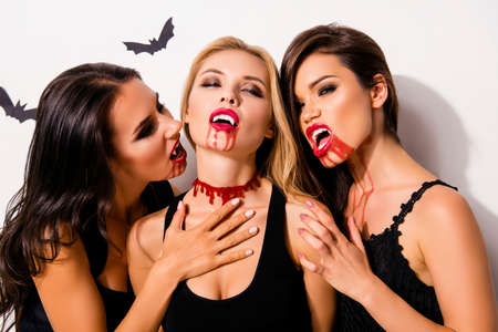 Photo for Anger, rage, death, hunger and thirst. Close up of three diabolic mysterious and paranormal mistress of the night attacking blond gothic satanic zombie, in dark dresses, on white background - Royalty Free Image