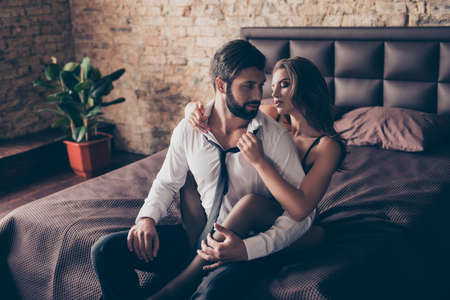 Photo pour Stunning brunette embracing her lover from the back, he is bearded handsome brunet in a formal wear, smiles. Lady is gorgeous and hot, brown sheets on bed, loft style room - image libre de droit