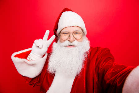 Foto de Taking holly jolly x mas festive memories. Funny Saint Nicholas photographer in red traditional outfit, head wear is showing peace gesture and makes shot on camera, isolated on red background - Imagen libre de derechos