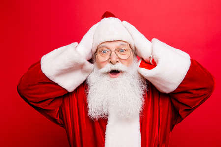 Foto de Discount, marketing, sales, gifts, promotion time! Holly jolly x mas is soon! Be ready, prepare! Gifts for kids! Amazed saint nicholas in red traditional outfit, head wear, isolated on red background - Imagen libre de derechos