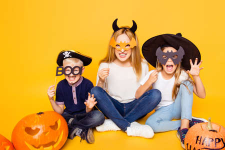 Photo for Close up portrait of mom with two small monsters, hiding behind eyemasks, with frightening gestures, sitting on the floor with crossed legs, handmade cutted pumpkin near, isolated on background - Royalty Free Image