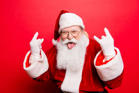 Photo pour It's party time! Holly jolly swag x mas and noel!  Cool funny playful naughty grandfather with sticking tongue, comic grimace, fooling around isolated on red background, shows rock gesture - image libre de droit