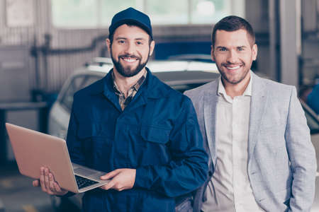 Foto de Two partners attractive guys, cheerful specialist repairman in blue costume, hat, holds his modern device, businessman in formal classy wear, blurred silver car behind. Vehicle breakdown, check - Imagen libre de derechos