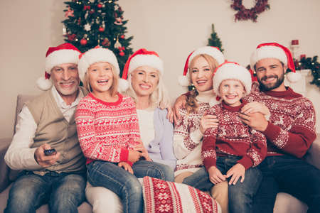 Photo pour Group of cheerful relatives embrace bonding on couch, married couples, excited siblings, grandad, granny, in knitted cute traditional x mas costumes,  pine firtree, home, movie, laugh - image libre de droit