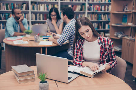 Foto de Focused concentrated attractive clever female student is learning with thesaurus in hard bookcase, wearing casual checkered shirt, behind her are classmates, book shelves of campus library - Imagen libre de derechos