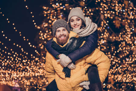 Photo for Handsome red bearded guy is piggy backing his cute lover, wearing winter warm outfits, head wear, behind them are x mas sparkles, holiday time, fun time together, love is in the air - Royalty Free Image