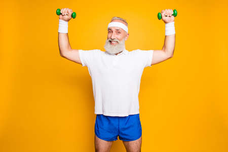 Foto de Cheerful cool grandpa with humor grimace exercising holding equipment up, lifts it with strength and power, wearing blue sexy shorts, so hot! - Imagen libre de derechos
