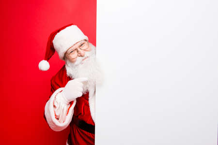 Photo for Advertisement, discounts, presents gifts selling december, winter tradition wish, eve, celebration of christmastime concept. Santa is standing near the white blank banner and points at side, empty - Royalty Free Image