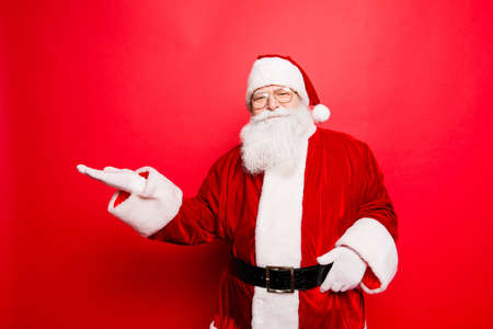 Foto de Sales, marketing, discounts, advertising, presents, gifts selling time! Holly jolly x mas is soon! Be ready, prepare! Saint nicholas is showing on side with arm, isolated on red background - Imagen libre de derechos