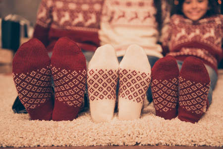 Foto de Close up cropped low angle of focus on three pairs of feet of festive husband and wife, baby girl, sitting down on floor, winter december feast x mas noel at coziness, in socks - Imagen libre de derechos