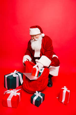 Foto de Holly jolly x mas noel time! Funny santa in headwear, costume, black belt, shoes, white gloves fills sack with a lot of gifts for kids, with ribbon tapes bows, digital devices - Imagen libre de derechos