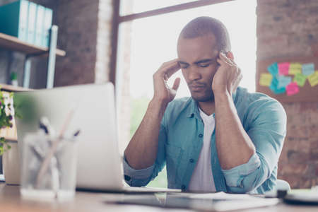 Photo for Overworked stressed mulatto freelancer is having headache and thinking how to end project. He is in a casual smart, at his home office - Royalty Free Image
