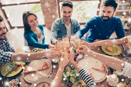 Foto de High angle view of friends at birthday party clinking glasses with champagne and toasting, enjoying xmas winter vacation, tasty dishes on the table, snowflakes background - Imagen libre de derechos