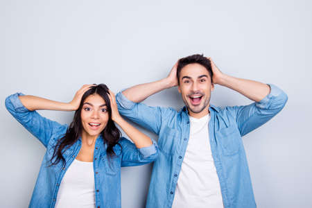 Photo pour Really? Portrait of two young shocked lovers are amazed with wide open eyes and mouth holding heads in casual wear standing over grey background - image libre de droit