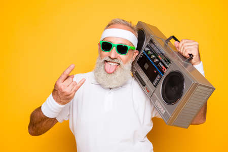 Photo pour Cheerful excited aged funny active sexy athlete cool pensioner grandpa in eyewear with bass clipping ghetto blaster recorder. Old school, swag, sticking tongue, fooling, gym, workout, technology - image libre de droit