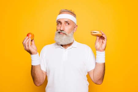 Foto de Athlete cool grandpa holds forbidden junkfood cheeseburger and fruit. Weightloss, decision, motivation, healthcare, strength, prohibition, workout, gym, regime, bodycare, calories lifestyle - Imagen libre de derechos