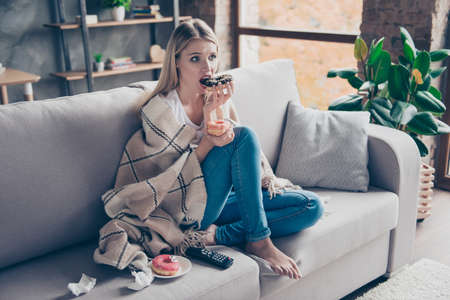 Photo for Beautiful blonde woman sitting on couch in living room under blanket eating chokolate donat watching something exciting interesting on television having health problem - Royalty Free Image